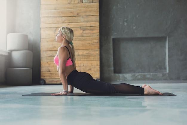 Kobieta, rozciąganie w sali do ćwiczeń, w pomieszczeniu. pełnej długości widok z boku sprawny dziewczyna w odzieży sportowej robi poranną gimnastykę