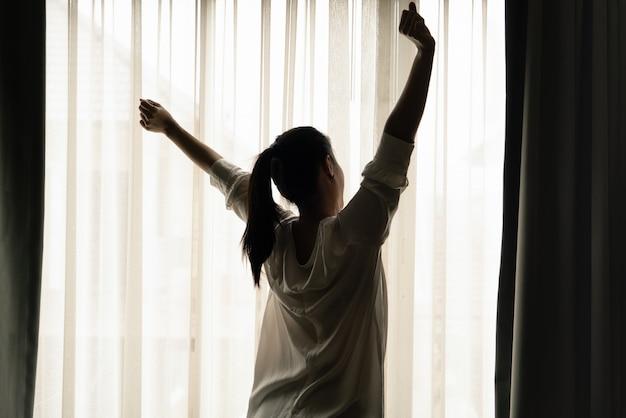 Kobieta rozciąganie w sypialni po obudzić, widok z tyłu