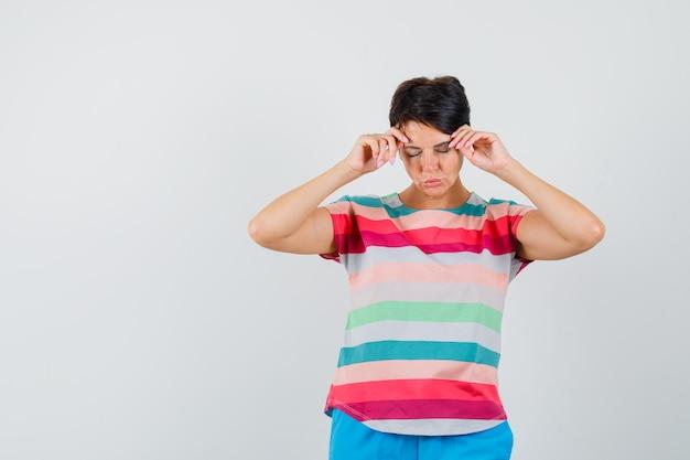 Kobieta rozcierająca skronie pasiastą koszulką, spodniami i wyglądająca na wyczerpaną. przedni widok.