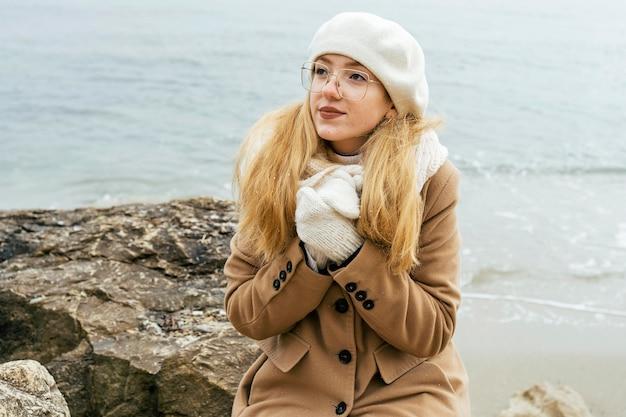 Kobieta rozgrzewa ręce na plaży zimą