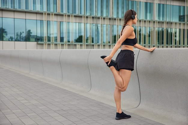 Kobieta rozgrzewa się przed joggingiem podnosi nogi rozciąga mięśnie ubrana w strój sportowy przygotowuje się do treningu cardio skoncentrowane do przodu pozy w pobliżu nowoczesnego budynku ze szkła miejskiego
