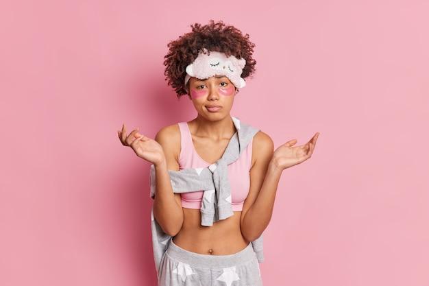 Kobieta rozkłada dłonie w talii i ma niezdecydowany wyraz twarzy, nakłada kolagenowe łaty pod oczy, aby zmniejszyć obrzęki, ubrana w swobodną piżamę odizolowaną na różowej ścianie studia