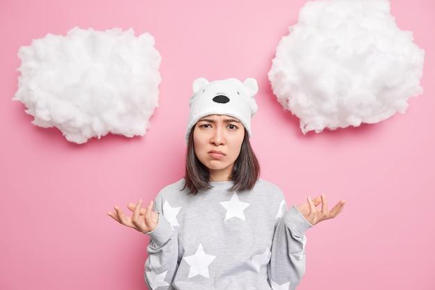 Kobieta rozkłada ręce ze zdziwionym, niezdecydowanym wyrazem twarzy nosi piżamę i niedźwiedzia czapkę odizolowane na różowo