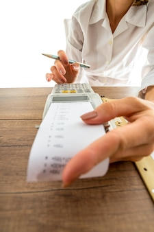 Kobieta rozlicza się na ręcznej maszynie do dodawania z niskim kątem widzenia poza wydrukowanym paskiem papieru do palców na klawiszach numerycznych.