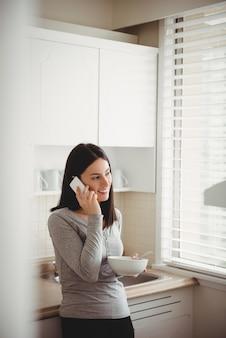 Kobieta rozmawia inteligentny telefon, trzymając miskę z jedzeniem