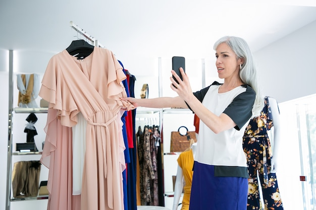 Kobieta rozmawia na komórce w sklepie z modą i pokazuje sukienkę na stojaku z przodu. sredni strzał. butikowy koncept klienta lub komunikacji