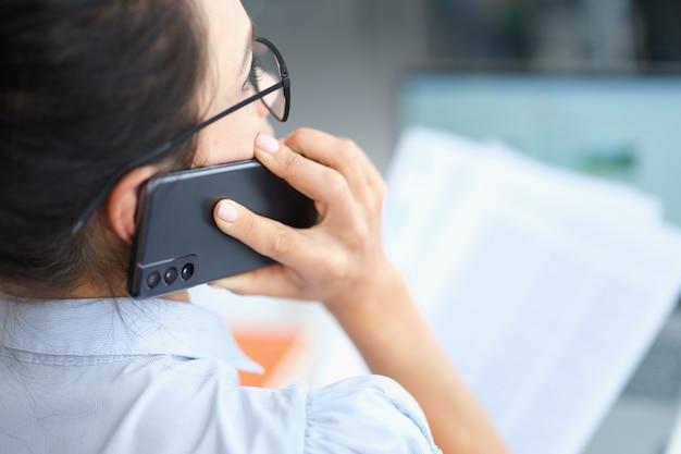 Kobieta rozmawia na smartfonie i czyta dokument rozwiązując problemy biznesowe firmy corporate