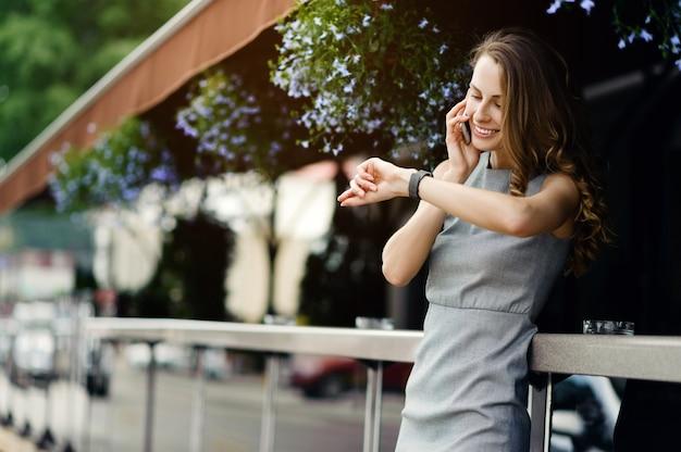 Kobieta rozmawia na smartfonie i sprawdza inteligentne zegarki na ulicy