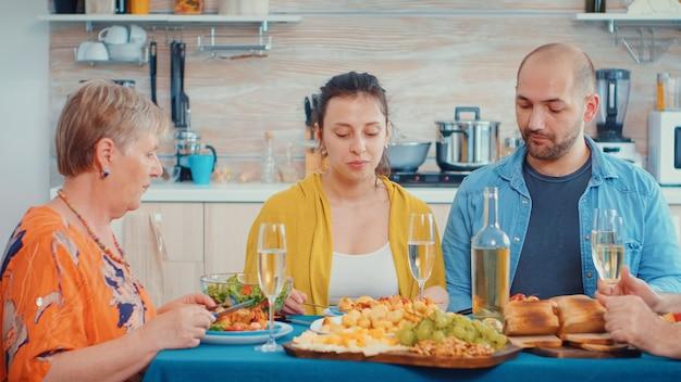 Kobieta rozmawia podczas kolacji. wielopokoleniowe, cztery osoby, dwie szczęśliwe pary rozmawiające i jedzące przy wykwintnym posiłku, ciesząc się czasem spędzonym w domu, w kuchni przy stole.