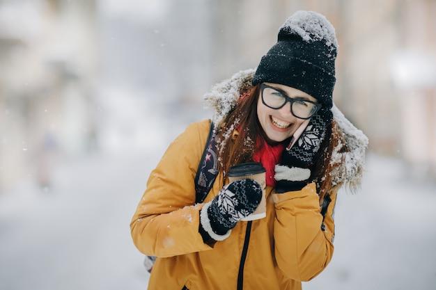 Kobieta rozmawia przez telefon i picia kawy. kobieta spaceru w zimie strrt i rozmawia przez telefon komórkowy