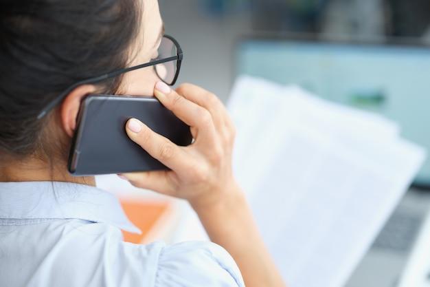 Kobieta rozmawia przez telefon i trzyma dokument w rękach praca zdalna i rozwiązywanie ważnych