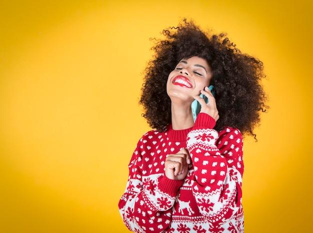 Kobieta rozmawia przez telefon komórkowy na boże narodzenie, żółte tło