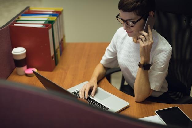 Kobieta rozmawia przez telefon komórkowy podczas korzystania z laptopa w biurze