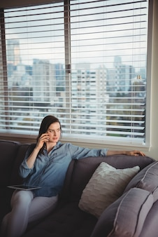 Kobieta rozmawia przez telefon komórkowy, siedząc na kanapie