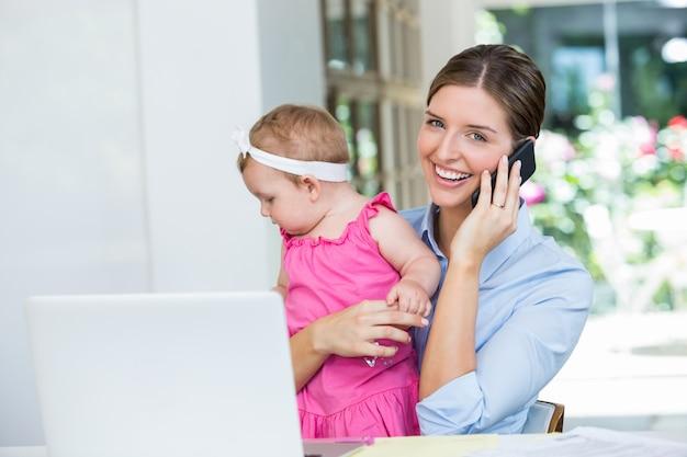 Kobieta rozmawia przez telefon komórkowy siedząc z córeczką