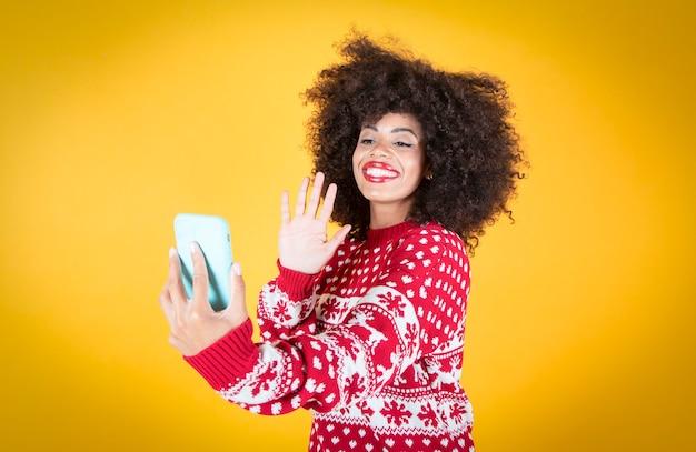 Kobieta rozmawia przez telefon komórkowy w czasie świąt bożego narodzenia, żółte tło