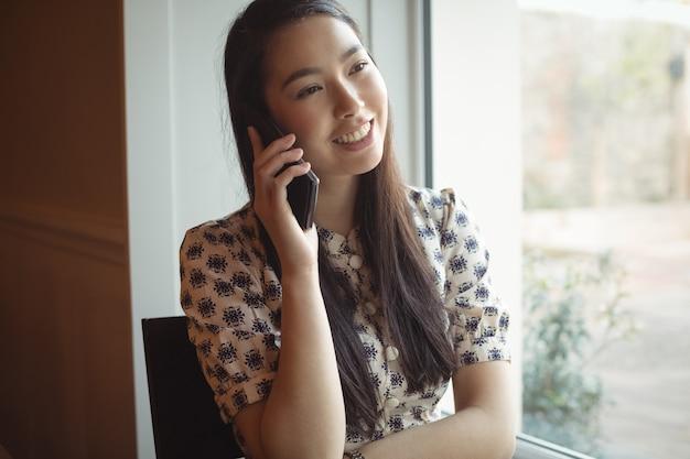Kobieta rozmawia przez telefon komórkowy w pobliżu okna
