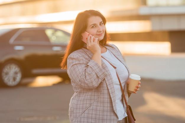 Kobieta rozmawia przez telefon na zewnątrz o zachodzie słońca