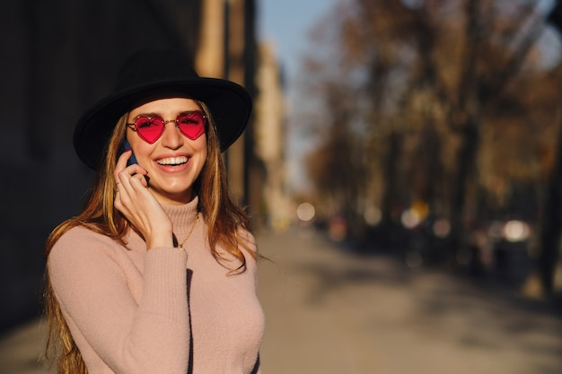 Kobieta rozmawia przez telefon na zewnątrz.