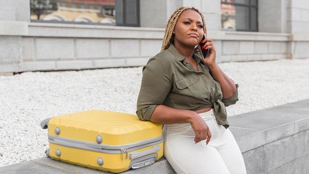 Kobieta rozmawia przez telefon obok swojego żółtego bagażu