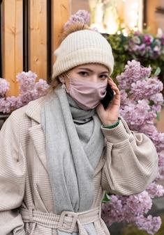 Kobieta rozmawia przez telefon podczas noszenia maski medycznej
