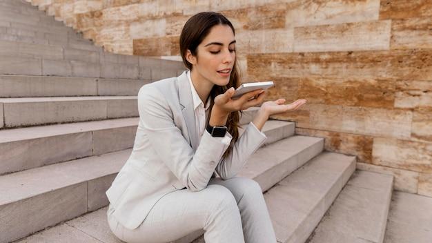 Kobieta rozmawia przez telefon siedząc na zewnątrz na schodach