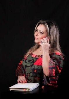 Kobieta rozmawia przez telefon stojący ze stołem i notatnikiem