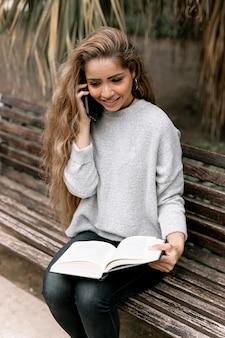 Kobieta rozmawia przez telefon, trzymając książkę