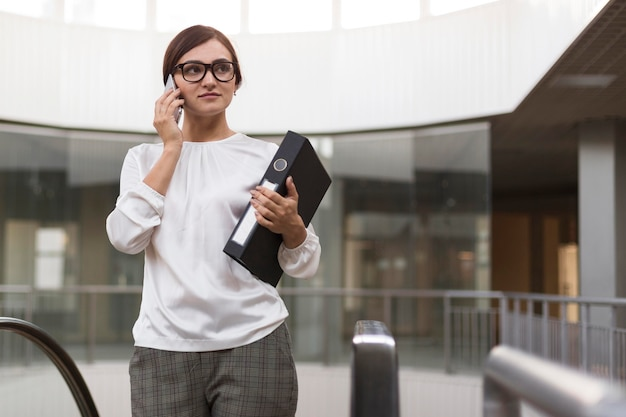 Kobieta rozmawia przez telefon trzymając segregator