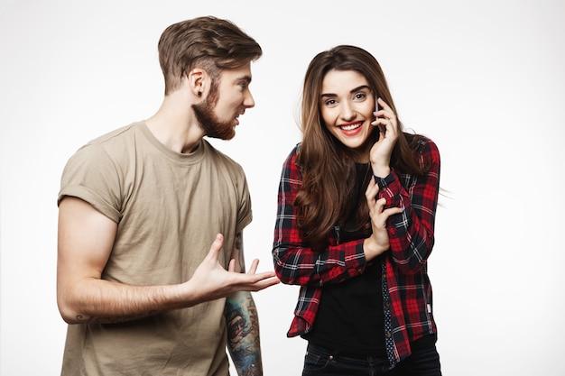 Kobieta rozmawia przez telefon, uśmiechając się radośnie obok przyjaciela