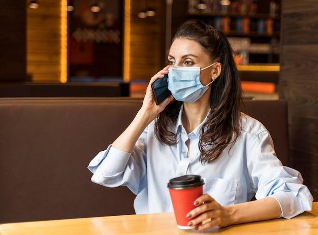 Kobieta rozmawia przez telefon w pomieszczeniu, mając na sobie maskę