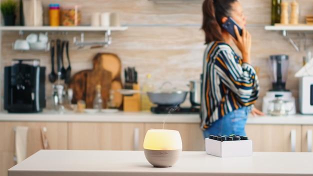 Kobieta rozmawia przez telefon z aromaterapią olejków eterycznych obok niej w kuchni. aromatyczna esencja zdrowotna, welness aromaterapia domowe spa zapach spokojna terapia, para terapeutyczna, zdrowie psychiczne