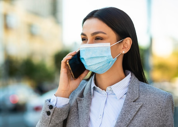 Kobieta rozmawia przez telefon z maską medyczną