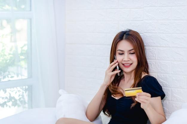 Kobieta rozmawia przez telefon za pomocą karty kredytowej