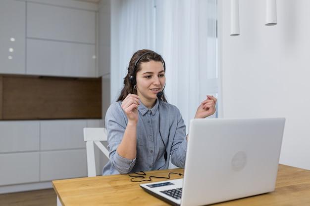 Kobieta rozmawia przez zestaw słuchawkowy poprzez książkę laptopa w biurze