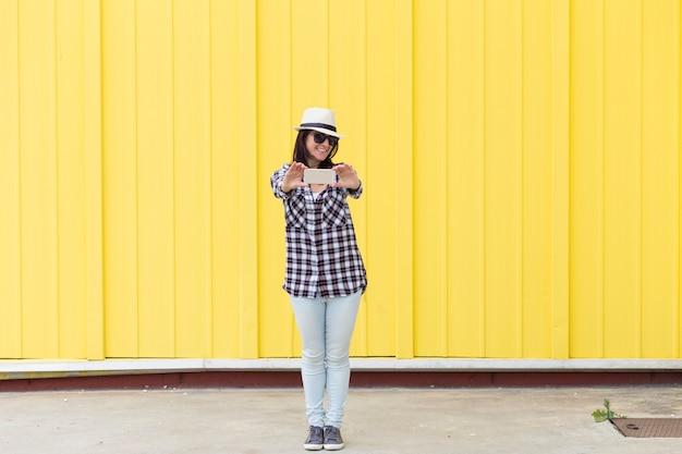 Kobieta rozmawia selfie z telefonu komórkowego na żółtym tle