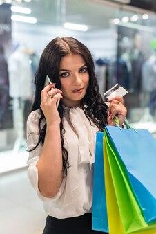 Kobieta rozmawia telefon z kartą kredytową i torby na zakupy
