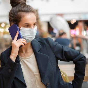 Kobieta rozmawia z maską medyczną na swoim telefonie