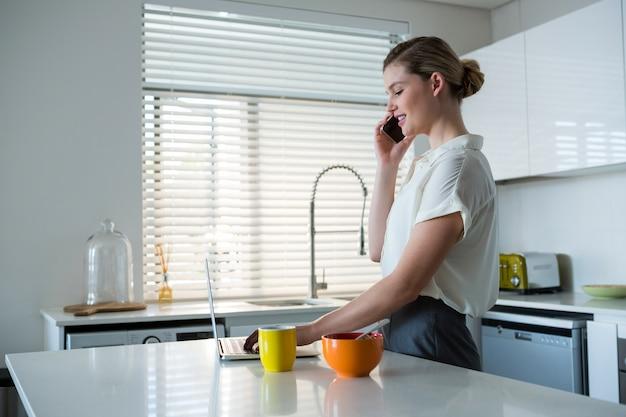 Kobieta rozmawia z telefonu komórkowego podczas korzystania z laptopa