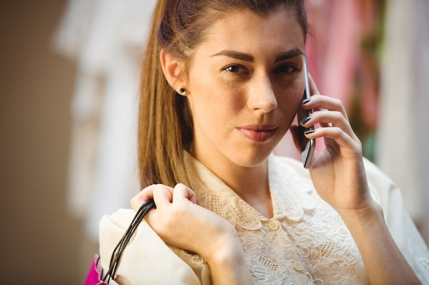 Kobieta rozmawia z telefonu komórkowego podczas robienia zakupów