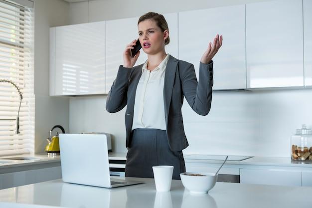 Kobieta rozmawia z telefonu komórkowego w kuchni