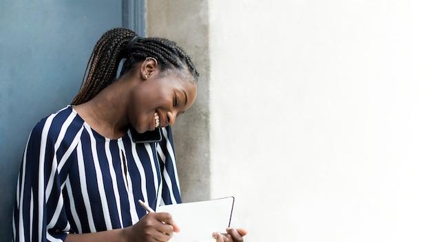 Kobieta rozmawiająca przez telefon podczas robienia notatek