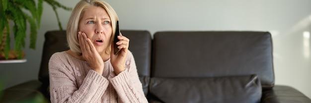 Kobieta rozmawiająca przez telefon, siedząca na kanapie w salonie w domu