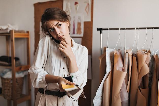 Kobieta rozmawiająca przez telefon, trzymająca próbki tkanin i w zamyśleniu pozująca