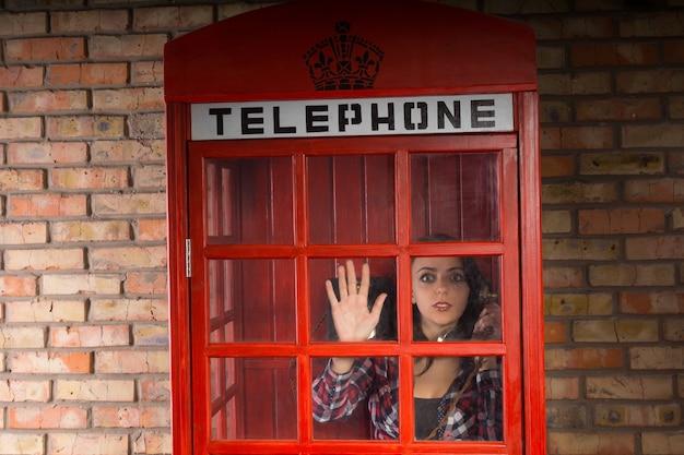 Kobieta rozmawiająca przez telefon wyglądająca z przerażenia z budki telefonicznej, gdy zauważa, że na zewnątrz dzieje się coś strasznego