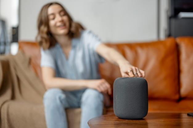 Kobieta rozmawiająca z kolumną asystenta audio