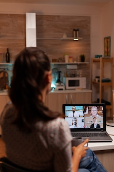 Kobieta rozmawiająca ze współpracownikami podczas wideokonferencji o północy z domu trzymająca filiżankę kawy...