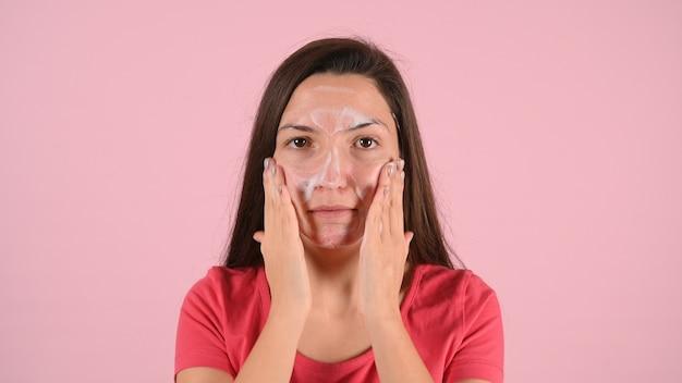Kobieta rozmazuje twarz kremem na trądzik na różowym tle