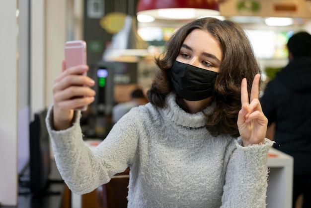 Kobieta rozmowy wideo podczas noszenia maski medycznej