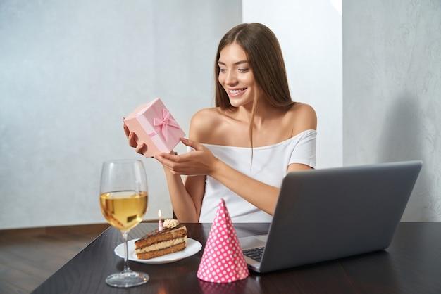 Kobieta rozpakowująca prezent podczas świętowania online